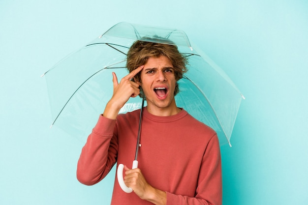 Young caucasian man with makeup holding umbrella isolated on blue background  showing a disappointment gesture with forefinger.