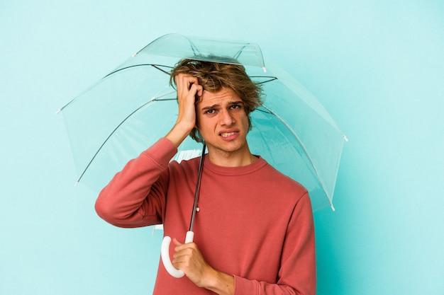 青い背景に孤立した傘を持って化粧をしている若い白人男性はショックを受けて、彼女は重要な会議を思い出しました。