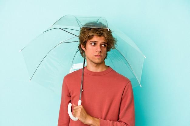 青い背景に孤立した傘を保持している化粧をしている若い白人男性は混乱し、疑わしく、不安を感じています。