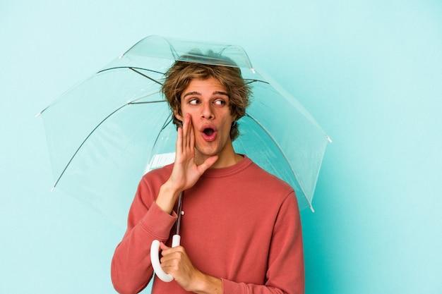 青い背景に分離された傘を保持している化粧をしている若い白人男性は、秘密のホットブレーキニュースを言って脇を見ています