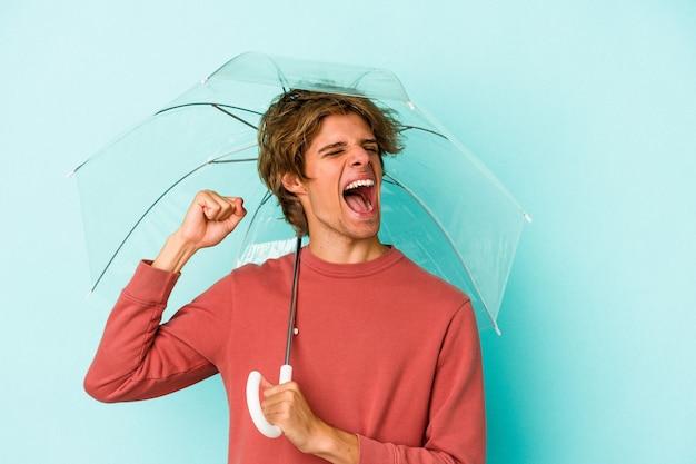 勝利、勝者の概念の後に拳を上げる青い背景に分離された傘を保持している化粧の若い白人男性。