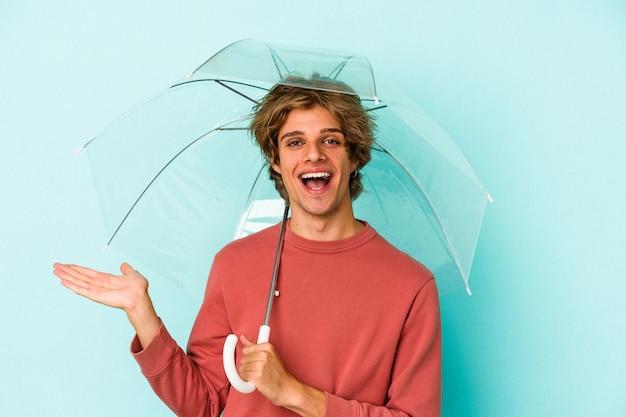Молодой кавказский человек с косметикой, держащей зонтик, изолированным на синем фоне, показывая копию пространства на ладони и держащую другую руку на талии.