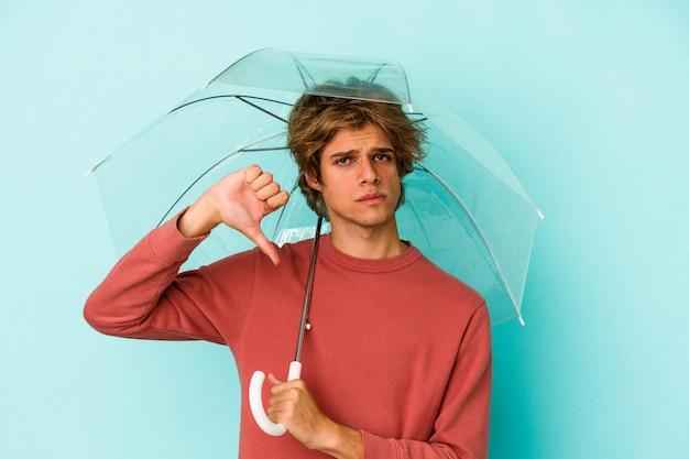 嫌いなジェスチャーを示す青い背景に分離された傘を持って化粧をしている若い白人男性は、親指を下に向けます。不一致の概念。