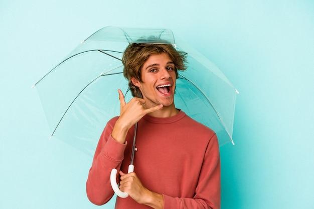 指で携帯電話の呼び出しジェスチャーを示す青い背景に分離された傘を保持している化粧をしている若い白人男性。