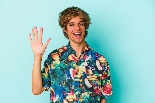 青い背景に分離された夏服を着て化粧をしている若い白人男性は、指で5番を示して陽気に笑っています。