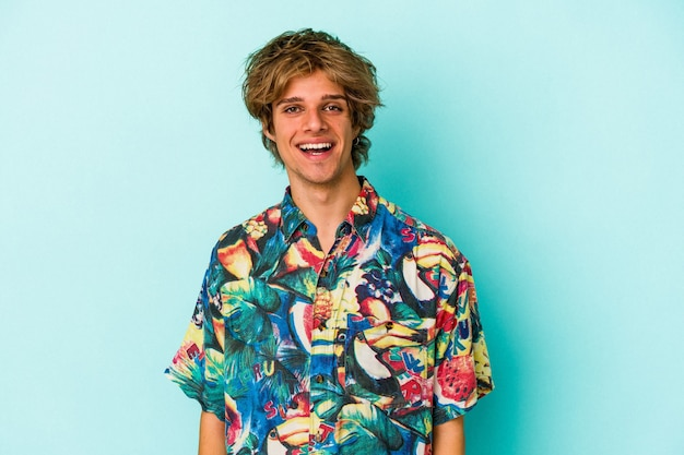 Young caucasian man with makeup wearing a summer clothes isolated on blue background  happy, smiling and cheerful.