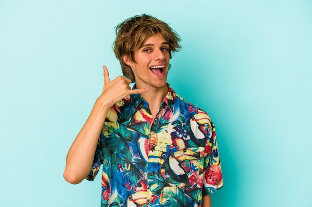 Young caucasian man with makeup wearing a summer clothes isolated on blue background  showing a mobile phone call gesture with fingers.