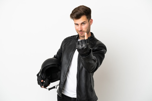Young caucasian man with a motorcycle helmet isolated on white background doing coming gesture