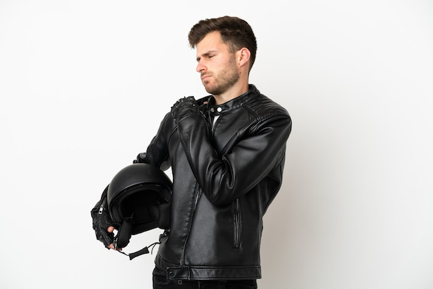 Young caucasian man with a motorcycle helmet isolated on white background suffering from pain in shoulder for having made an effort