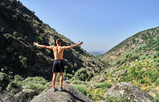 山のある素敵な風景の中で両手を広げて若い白人男性。