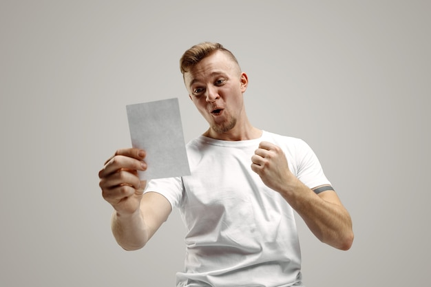 Young caucasian man with a surprised happy expression won a bet on gray studio background. human facial emotions and betting concept