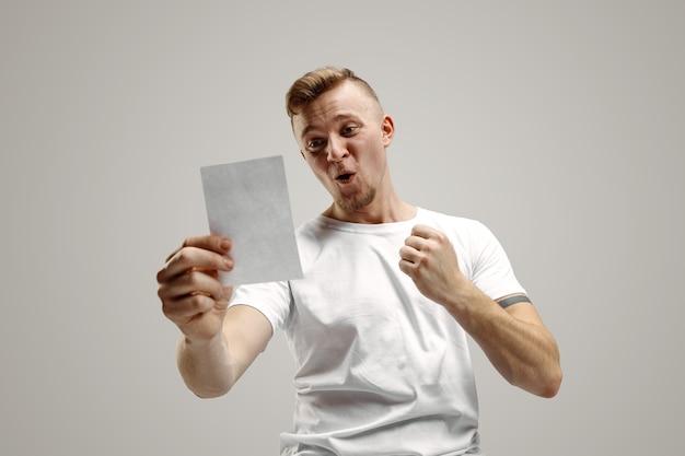 Il giovane uomo caucasico con un'espressione felice sorpresa ha vinto una scommessa su sfondo grigio studio. emozioni facciali umane e concetto di scommesse