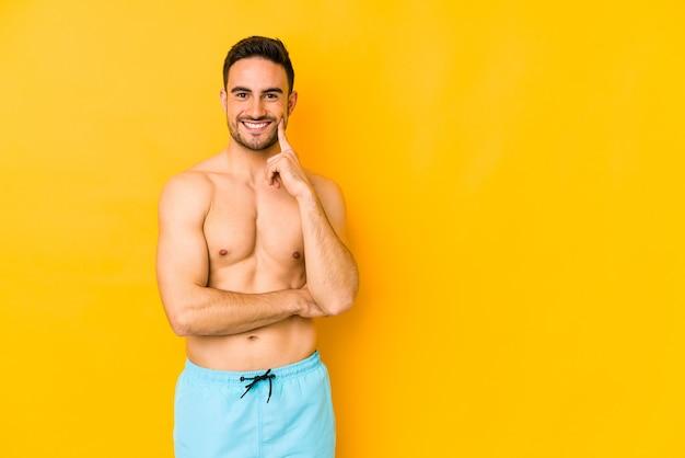 黄色の背景に分離された水着を持つ若い白人男手であごに触れる幸せで自信を持ってtrsmilingを持つ若い白人男。
