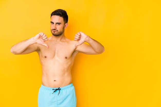 Young caucasian man with swimsuit isolated on yellow space young caucasian man with trshowing thumb down, disappointment concept.