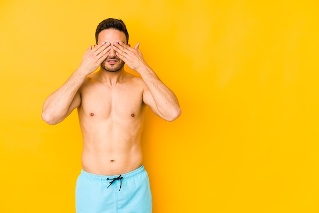 Young caucasian man with swimsuit isolated on yellow wall young caucasian man with afraid covering eyes with hands.