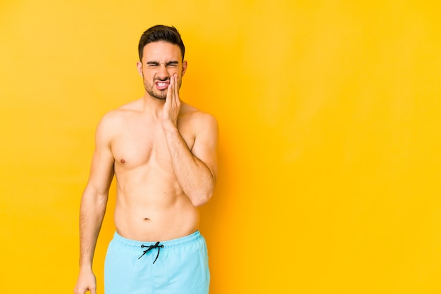 Young caucasian man with swimsuit isolated on yellow wall young caucasian man with trhaving a strong teeth pain, molar ache.