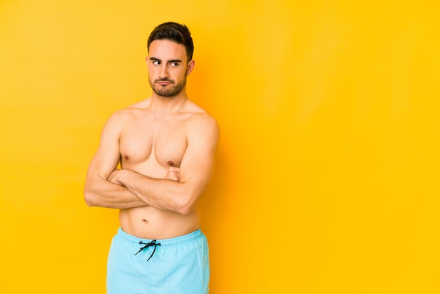 Young caucasian man with swimsuit isolated on yellow