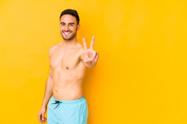 水着で若い白人男指で平和のシンボルを示すうれしそうな屈託のない若い白人男。