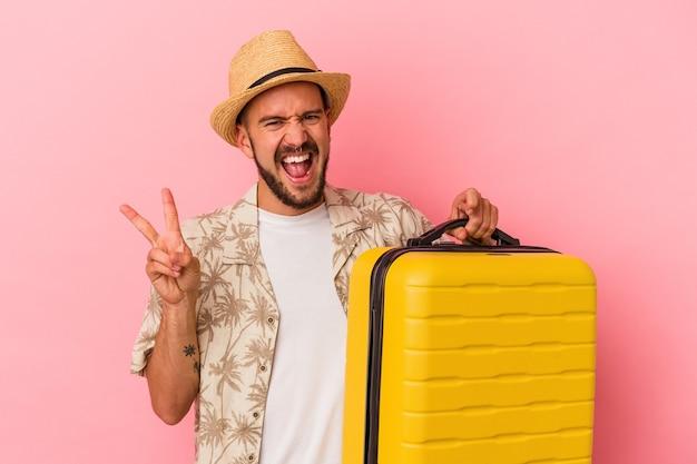 ピンクの背景に孤立した旅行に行く入れ墨のある若い白人男性は、指で平和のシンボルを示して楽しくてのんきです。