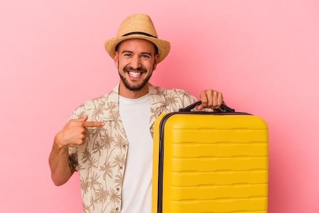 ピンクの背景の人がシャツのコピースペースを手で指して、誇りと自信を持って旅行に行く入れ墨を持つ若い白人男性