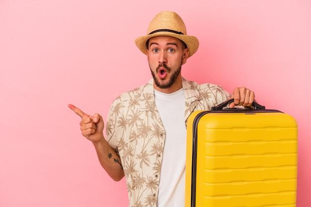 側面を指しているピンクの背景に孤立して旅行に行く入れ墨を持つ若い白人男性