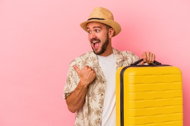 문신을 한 젊은 백인 남자는 분홍색 배경에 고립되어 엄지손가락을 치켜들고 웃고 근심 걱정 없이 여행할 것입니다.