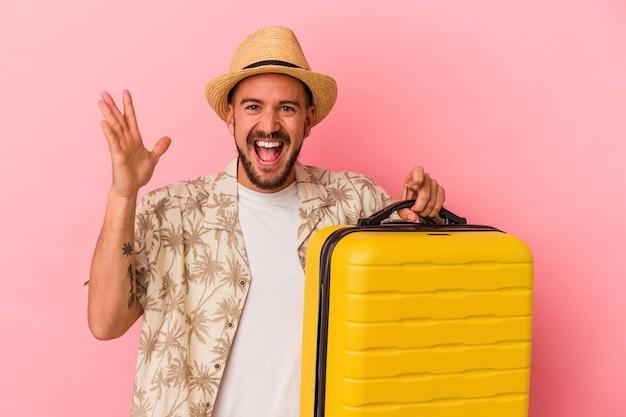 ピンクの背景に孤立して旅行に行く入れ墨の若い白人男性は、嬉しい驚きを受け取り、興奮し、手を上げます。