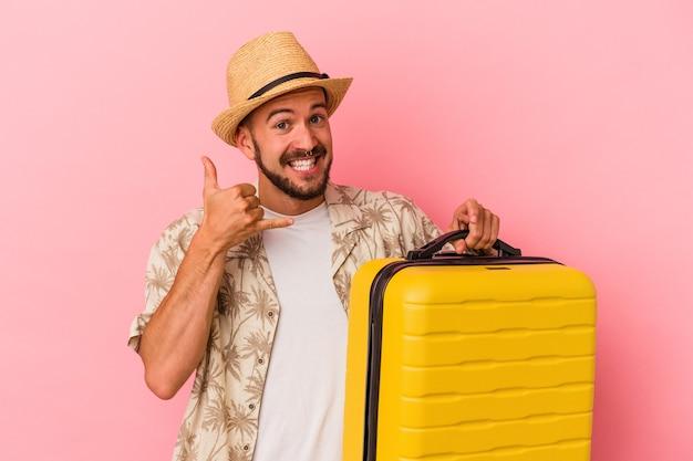 指で携帯電話の呼び出しジェスチャーを示すピンクの背景に孤立して旅行に行く入れ墨を持つ若い白人男性。