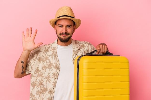 ピンクの背景に孤立して旅行に行く入れ墨の若い白人男性は、指で5番を示して陽気に笑っています。 Premium写真
