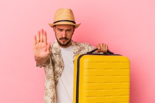 ピンクの背景に孤立して旅行に行く入れ墨の若い白人男性は、一時停止の標識を示している手を伸ばして立って、あなたを防ぎます。