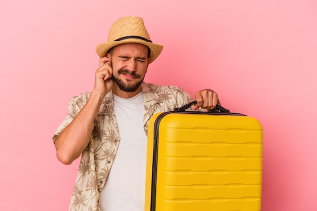 Young caucasian man with tattoos going to travel isolated on pink background  covering ears with hands.