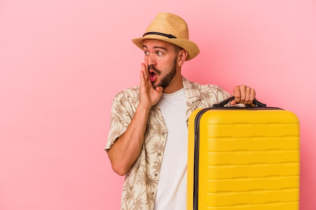 Young caucasian man with tattoos going to travel isolated on pink background  is saying a secret hot braking news and looking aside