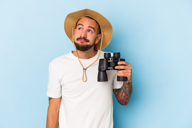 Young caucasian man with tattoos holding binoculars isolated on blue background  dreaming of achieving goals and purposes