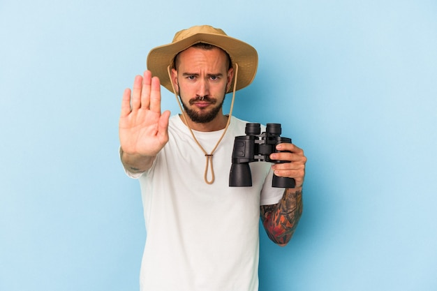 Young caucasian man with tattoos holding binoculars isolated on blue background  standing with outstretched hand showing stop sign, preventing you.