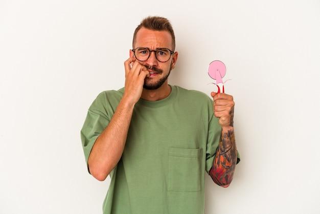 指の爪を噛んで、神経質で非常に心配している白い背景に分離されたロリポップを保持している入れ墨を持つ若い白人男性。