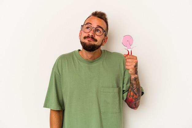 目標と目的を達成することを夢見て白い背景で隔離のロリポップを保持している入れ墨を持つ若い白人男性