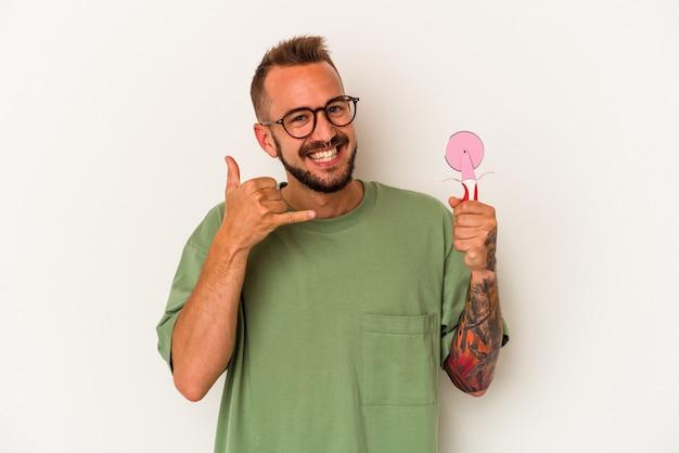 指で携帯電話の呼び出しジェスチャーを示す白い背景で隔離のロリポップを保持している入れ墨を持つ若い白人男性。