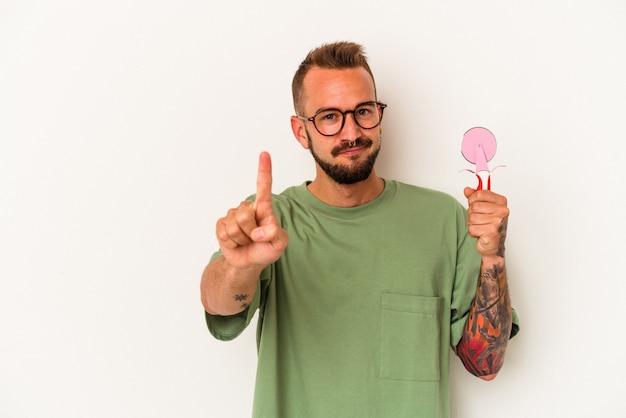 指でナンバーワンを示す白い背景で隔離のロリポップを保持している入れ墨を持つ若い白人男性。