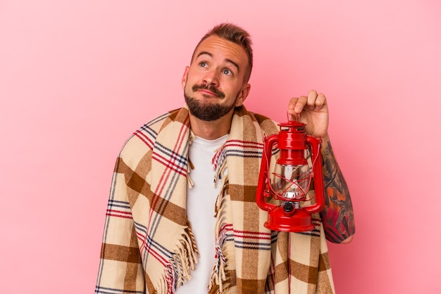 Young caucasian man with tattoos holding vintage lantern isolated on pink background  dreaming of achieving goals and purposes