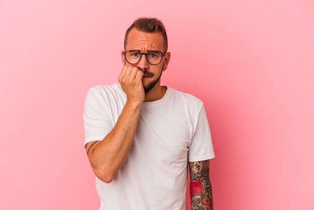 분홍색 배경에 문신을 한 젊은 백인 남자는 손톱을 물어뜯고 긴장하고 매우 불안해합니다.