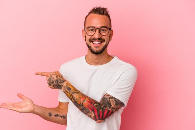 ピンクの背景に分離された入れ墨を持つ若い白人男性は、手のひらにコピースペースを保持して興奮しました。