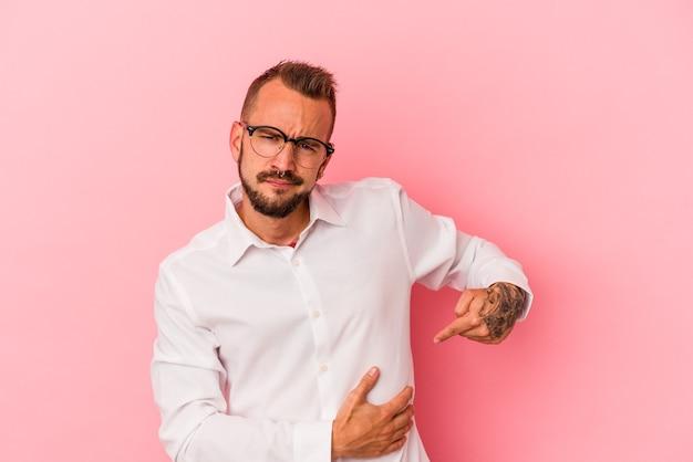 肝臓の痛み、胃の痛みを持っているピンクの背景に分離された入れ墨を持つ若い白人男性。
