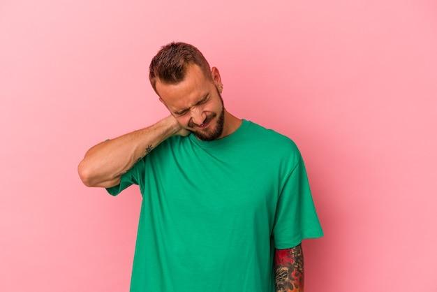 ピンクの背景に隔離された入れ墨の若い白人男性は、ストレス、マッサージ、手でそれに触れることによる首の痛みを持っています。