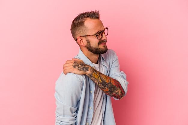 肩の痛みを持っているピンクの背景に分離された入れ墨を持つ若い白人男性。