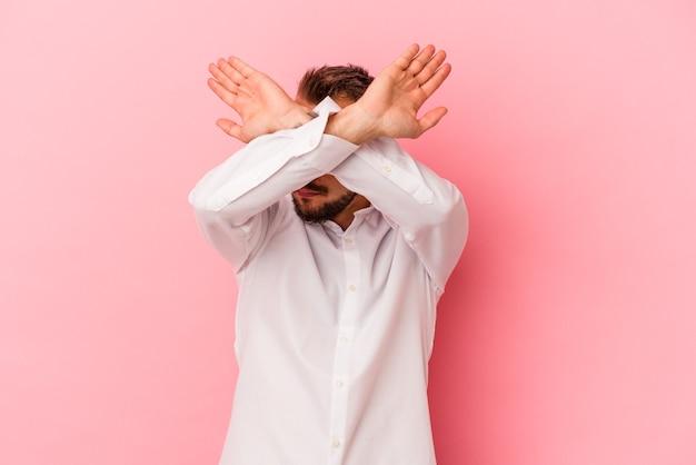 ピンクの背景に分離された入れ墨を持つ若い白人男性は、2つの腕を交差させたまま、概念を否定します。