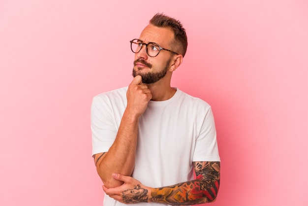 疑わしいと懐疑的な表現で横向きに見えるピンクの背景に分離された入れ墨を持つ若い白人男性。