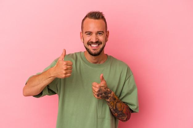 ピンクの背景に分離された入れ墨を持つ若い白人男性は、両方の親指を上げて、笑顔で自信を持っています。