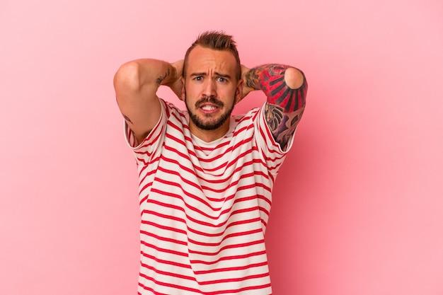 Молодой кавказский человек с татуировками, изолированными на розовом фоне, кричит от ярости.