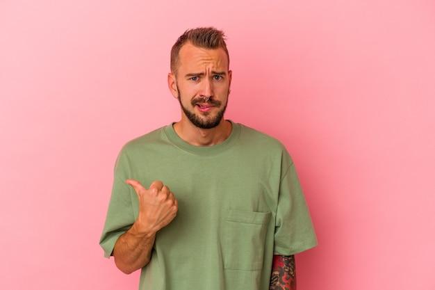 Молодой кавказский мужчина с татуировками, изолированными на розовом фоне, потрясен, указывая указательными пальцами на место для копирования.