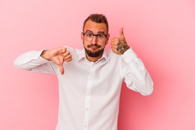 親指を上に、親指を下に表示するピンクの背景に分離された入れ墨を持つ若い白人男性、難しい選択の概念